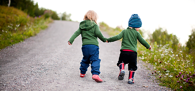 Two children walking on a road holding each other's hands, seen from behind.
