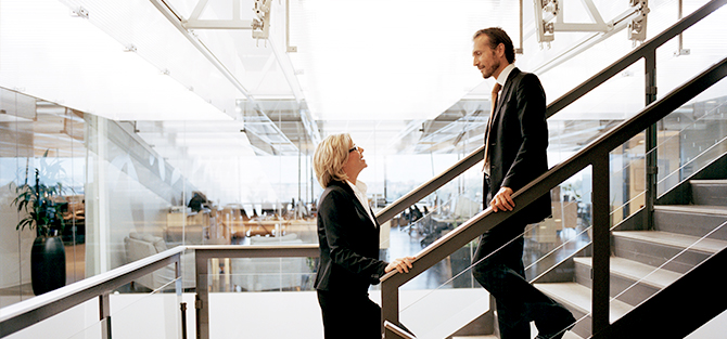 Woman and man in stairs in office environment.